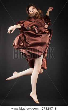 Beautiful dancer jumping on dark background