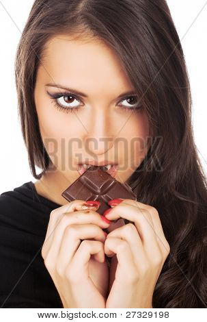 Portrait of young serious woman eating chocolate