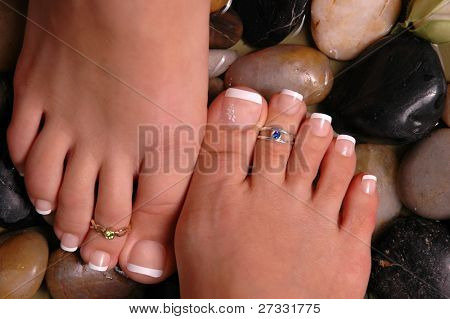 Two pedicured feet on healing pebbles