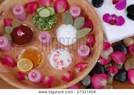 Face masks, bath salt, body scrubs, petals, orchids, towels, and pebbles in a spa