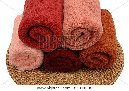 Five colorful towels on a rattan plate