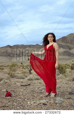 A girl wearing a red evening gown in the desert