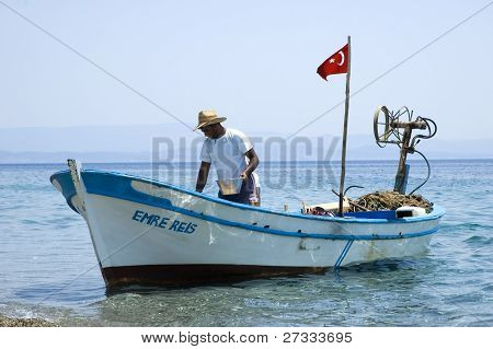 A fisherman selling fish he caught at the Aegean sea