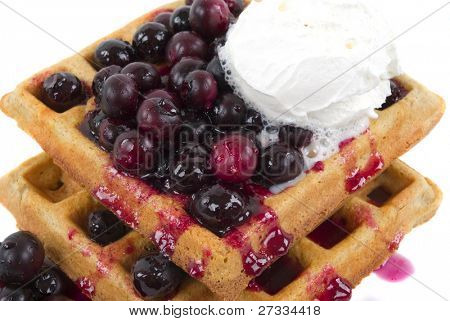 Organic hot wheat waffles with organic fresh blueberries, honey and cream