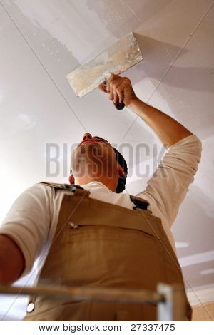 Man putting up a plasterboard ceiling