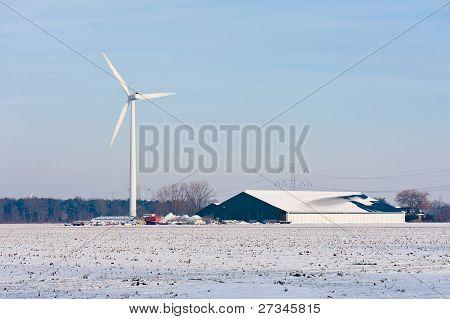 Dutch Farmhouse With Windturbine In Wintertime
