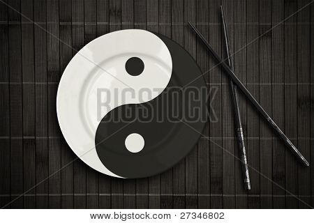 yin yan plate over bamboo placemat setting with chopsticks