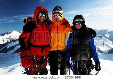 Team of alpinists celebrating on a peak