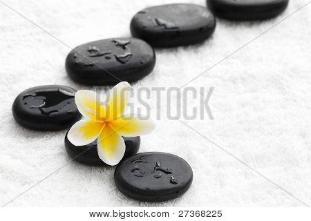 zen stones with frangipani flower on white towel