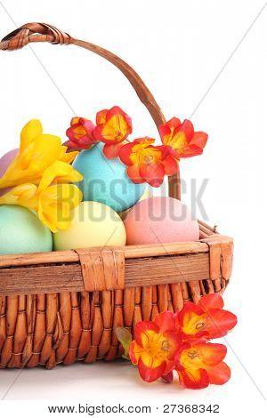 Basket full of easter eggs and spring flower