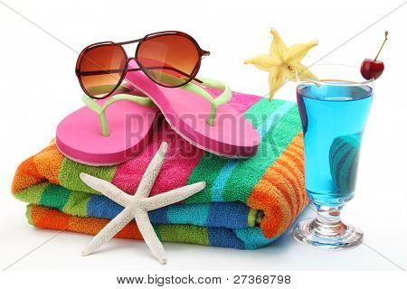 Beach items with towel,flip flops, sunglasses and a glass of cocktail.Isolated on white background.