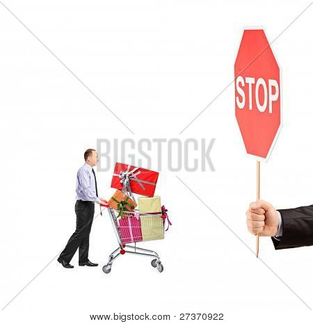 Man pushing a shopping cart full with gifts and a hand holding a stop sign isolated on white background