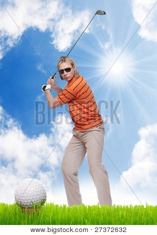 Golfer on a green against sunny sky.