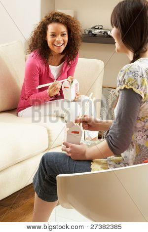 Two Female Friends Enjoying Chinese Takeaway Meal At Home