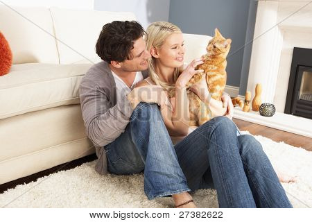 Couple Taking Playing With Pet Cat At Home