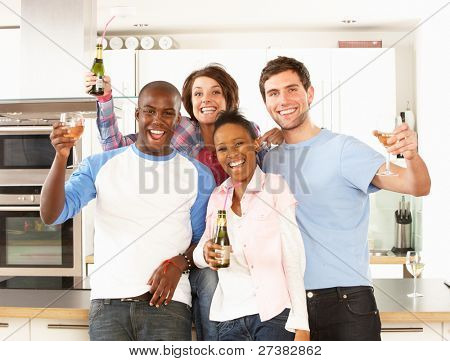 Group Of Young Friends Enjoying Drink In Modern Kitchen