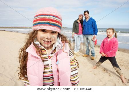 Family Walking Along Winter Beach