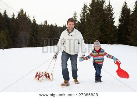 Jung-Vater und Tochter, Wandern im Schnee mit Schlitten