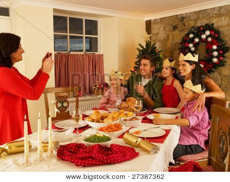 Hispanic family taking photos of Christmas dinner
