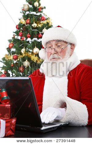 real Santa Claus working on laptop with surprised face, isolated on white background