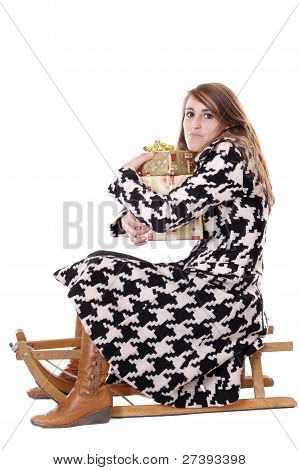 Young Woman In Black & White Coat On Sledge With Gifts