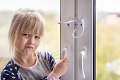 Little Cute Toddler Girl Trying To Open Window In Apartment At High-tower Building. Children Window  poster