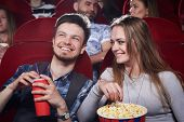 Happy Cute Couple Eating Popcorn And Laughing At Funny Comedy In Cinema Theater. Attractive Girl And poster