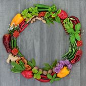 Herb and spice wreath with a selection of dried and fresh herbs and flowers on rustic wood backgroun poster