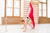 Slim female in activewear practicing yoga exercises or acrobatics with resistance band poster