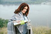 Portrait Of Girl With Thermos Pours Hot Tea Into Mug On Meadow On Background Of River At Misty Morni poster