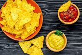 Snack For Party. Mexican Nachos Near Salsa And Guacamole Sause On Black Background Top View poster