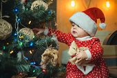 Christmas Babies. Christmas Children. Cute Little Child Is Decorating Christmas Tree Indoors. Happy  poster