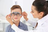 Childrens Doctor Putting Trial Frame On Little Boy In Clinic. Eye Examination poster