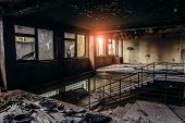 Burned Interiors After Fire In Industrial Or Office Building. Walls And Staircase In Black Soot, Fir poster