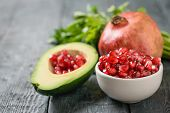 Half Avocado With Pomegranate Seeds, Bowl With Pomegranate Seeds, Ripe Pomegranate And Parsley On A  poster