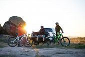 Cyclists Friends are Resting on the Pickup Offroad Truck after Bike Riding in the Mountains at Warm  poster