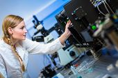 Female researcher carrying out research in a physics/chemistry lab (color toned image; shallow DOF) poster
