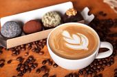 Close-up Of A Cup Of Latte Or Cappuccino With Latte Art. Coffee And Cakes On A Wooden Table With Sca poster