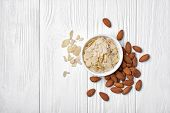 Top View Of Almond Slices And Whole Nut In White Bowl On Wooden Background poster
