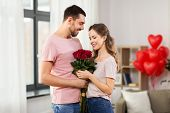 valentines day, relationships and people concept - happy couple with bunch of flowers hugging at hom poster
