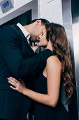 Man In Suit Passionately Kissing Beautiful Woman Near Elevator poster