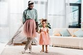 Happy African American Father And Adorable Daughter Dancing In Pink Tutu Skirts poster