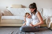 Cute Small Boy With Down Syndrome Playing With Mother In Home Living Room poster