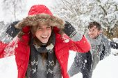 picture of snowball-fight  - Young couple having snowball fight - JPG