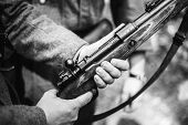 Re-enactor Dressed As World War Ii German Soldier Holding Rifle. Photo In Black And White Colors. So poster