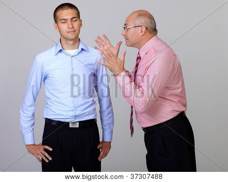 Senior and junior businessman discuss and argue over something during their meeting, isolated on grey