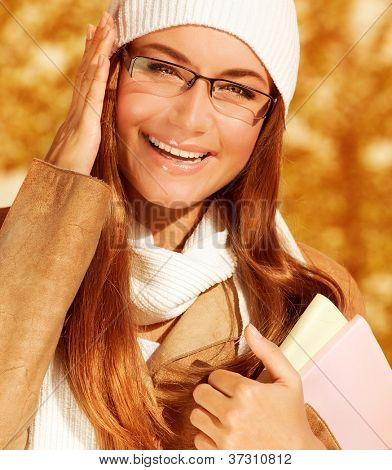 Photo of beautiful happy student girl holding textbook, closeup portrait of young stylish businesswoman wearing warm white hat and scarf, pretty teen in glasses on orange autumn background
