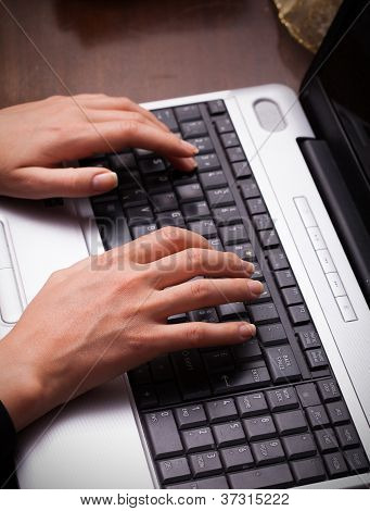 Closeup Of Female Hands Typing On Laptop Keypad