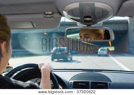 Mulher jovem, condução de carro na autobahn, vista de dentro do auto