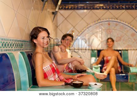 Three friends - two women, one man - doing wellness in the sauna of a thermal bath